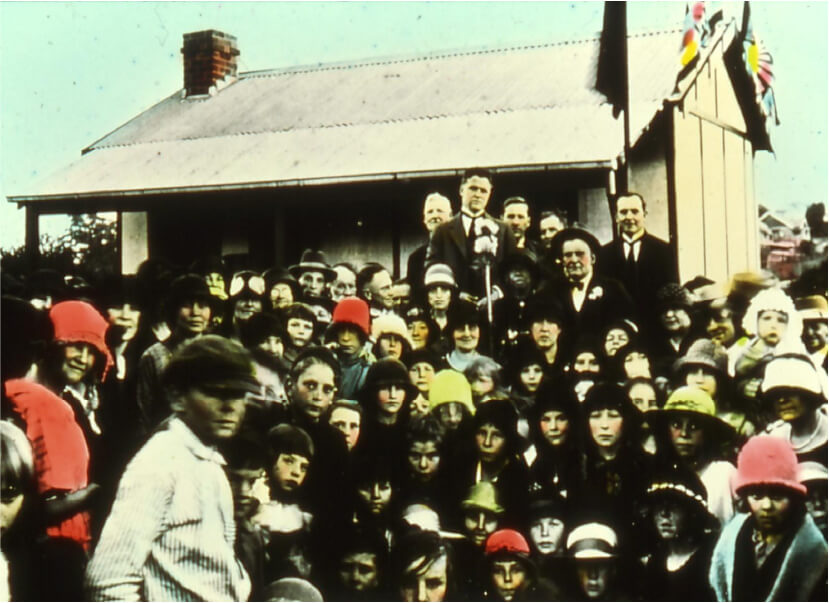 Lucy Willeri standing beside the Mayor at the Cottage Handover on 1 August 1925, holding a black kewpie doll.